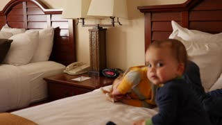 An interior dolly shot of cute family on hotel room bed