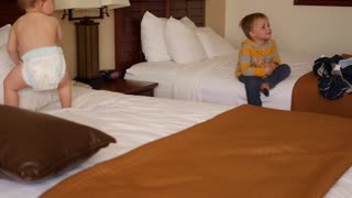 An interior panning shot of cute boys on hotel room bed