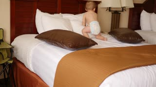 An interior panning shot of cute family on hotel room bed