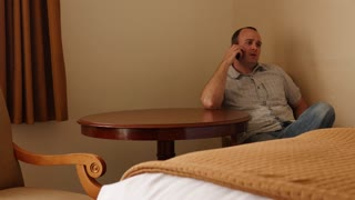 An interior shot of a man on phone in hotel room
