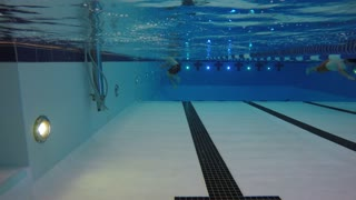 An underwater shot man swimming toward a camera