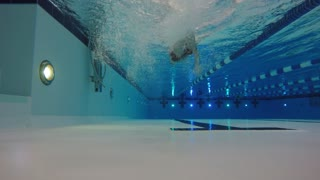 An underwater shot of a man swimming for camera