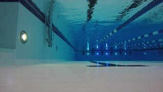 An underwater shot of man swimming freestyle in a pool