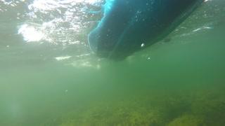 An underwater shot of sea kayak on surface of ocean