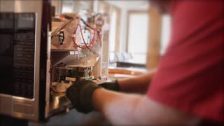 Appliance technician looks at microwave circuit boards