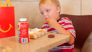 Boy eating chicken nuggets and french fries with chocolate milk