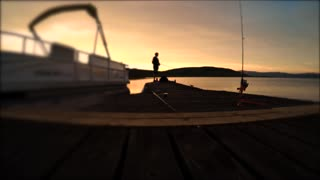 Boy fishing with a pole off a dock at sunse