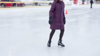 Boy Ice Skating With His Family On A Rink