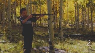 Boy shooting his bb gun while camping