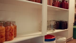 canned food in jars in storage shelf