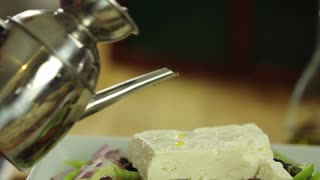 chef puts oil on feta cheese on a greek salad