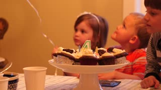 Children eating cupcakes for a birthday party celebration