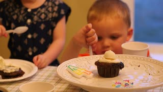 Children eating cupcakes for birthday party celebration