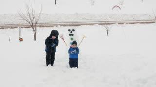 Children Make A Snowman In Their Yard