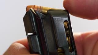 Closeup man unloads bullets from magazine