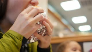 Closeup Shot Of A Woman Eating A Hamburger At Fast Food Place