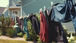 Clothes hang on a line blowing in a wind