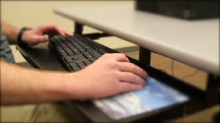 College student typing on computer keyboard