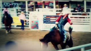 Cowboy riding bareback at rodeo
