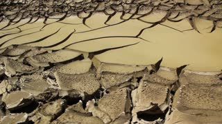 Cracked desert leading to water
