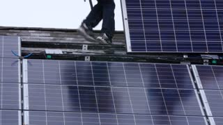 Crews placing solar panels on a roof of a house