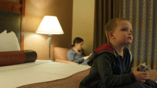 Cute Little Boy Watching Tv In A Hotel Room At Night With His Mother