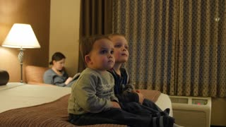 Cute Little Boys Watching Tv In A Hotel Room At Night With Their Mother