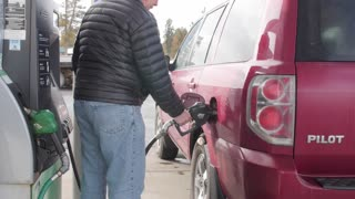 Dolly Shot Of A Man Filling Up A Car With Gas