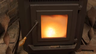 Dolly Shot Of A Pellet Stove Heating A Room