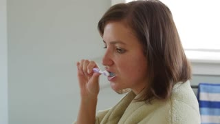 Dolly shot of a woman brushing her teeth in robe