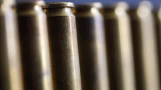 Dolly shot of large caliber bullets in a production line