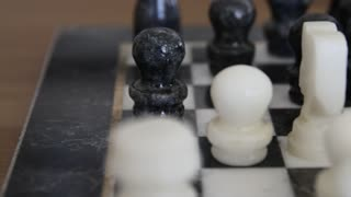 Dolly shot of marble chess pieces on chess board