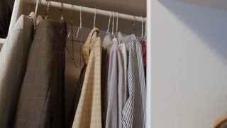 Dolly shot of mens dress shirts hanging up in a closet