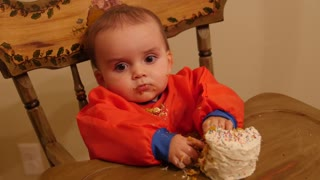 Dolly shot of messy baby boy eating his birthday cake at home