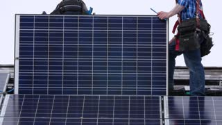 Editorial a crew placing solar panels on roof