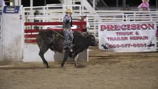 Editorial cowboy riding a big bull at the PRCA Oakley rodeo slow motion