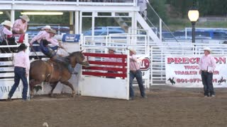 Editorial cowboy riding saddle bronc in a PRCA rodeo slow motion