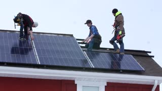 Editorial crews placing solar panels on a roof of a house