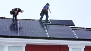 Editorial crews placing solar panels on the roof of a house