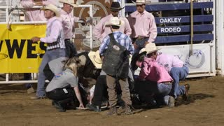 Editorial medical staff help an injured bull rider at a PRCA rodeo