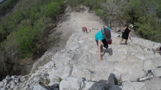 Editorial people climb big stairs at Ek Balam Mayan ruins in Mexico