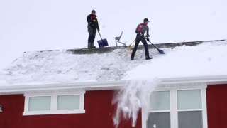 Editorial two men shovel off roof for solar panels