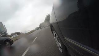 Exterior low shot cars driving in Provo city Utah through rain