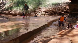 Families playing in desert river