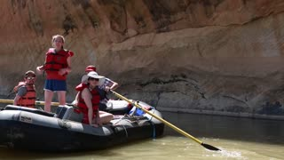 families rowing river rafts down san juan river by cliff