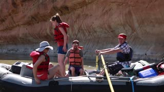 families rowing river rafts down the san juan river by cliff