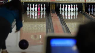 Family bowls in small town bowling alley