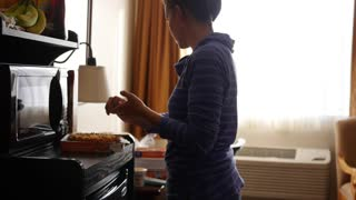 Family cooking microwave pizzas for dinner in hotel