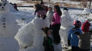 Family makes snow men and a slide from snow