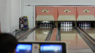 Family playing a game of bowling in an small bowling alley